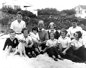 """The Kennedy Family at Hyannis Port, 1931. L-R: Robert Kennedy, John F. Kennedy, Eunice Kennedy, Jean Kennedy (on lap of) Joseph P. Kennedy Sr., Rose Fitzgerald Kennedy (behind) Patricia Kennedy, Kathleen Kennedy, Joseph P. Kennedy Jr. (behind) Rosemary Kennedy. Dog in foreground is """"Buddy"""". Photograph by Richard Sears in the John F. Kennedy Presidential Library and Museum, Boston."""