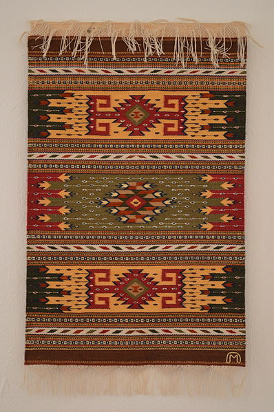 Woven rug of cotton and silk in tradicional design by Arnulfo Mendoza at the Museo de los Pintores Oaxaqueños in the city of Oaxaca. Attribution:  AlejandroLinaresGarcia