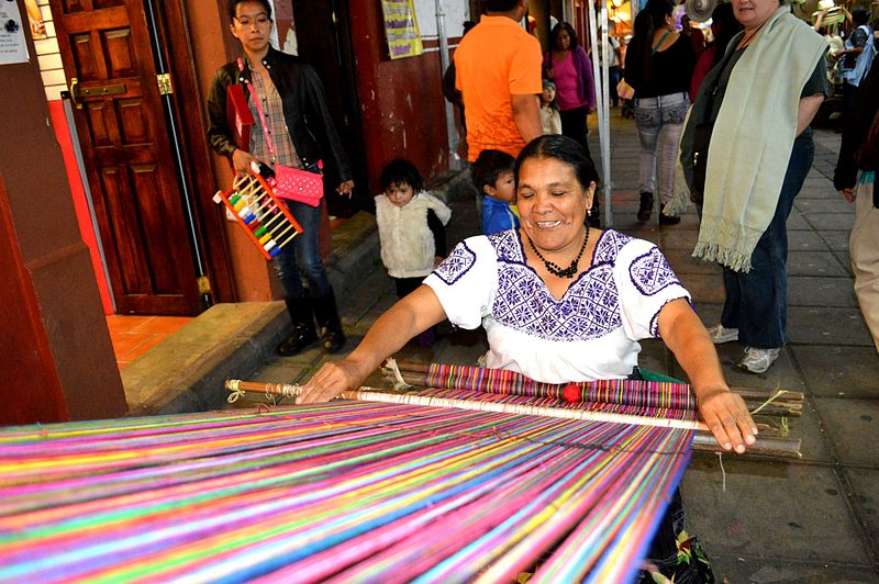 Indigenous women weaving on a backstrap loom during the Tianguis de Domingo de Ramos in Uruapan, Michoacan, Mexico. Attribution: AlejandroLinaresGarcia
