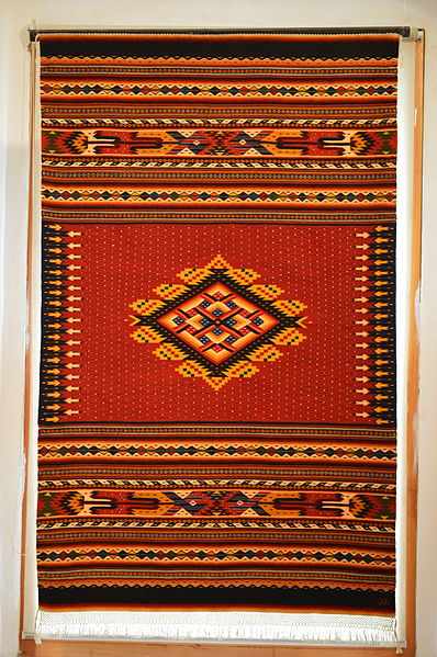 Woven rug in traditional design at the exhibition La Mano Mágica by Arnulfo Mendoza at the Museo de los Pintores Oaxaqueños in the city of Oaxaca, Mexico. Attribution: AlejandroLinaresGarcia