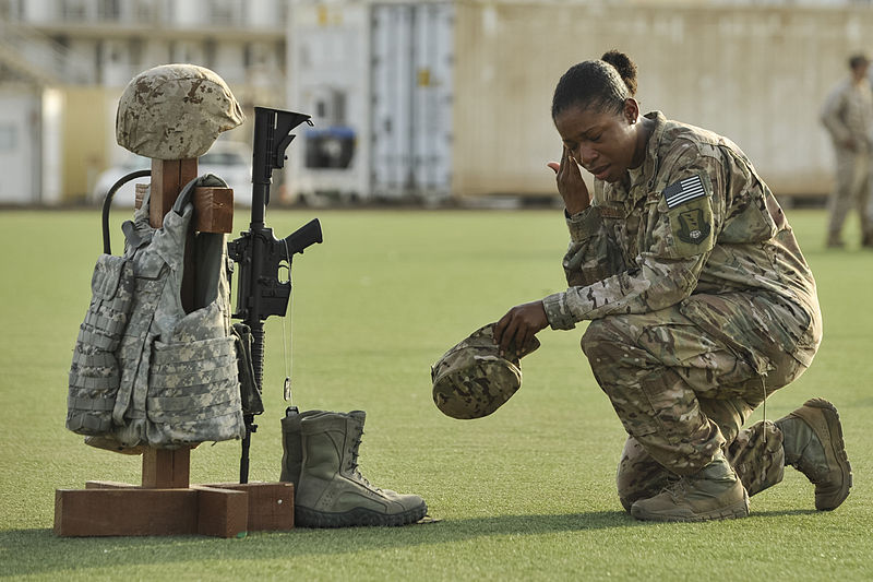 MPOTY_2014_U.S._Air_Force_Master_Sgt._kneels_in_front_of_a_battlefield_cross